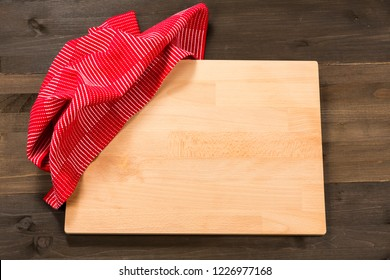 Cutting board and checkered tablecloth isolated on wooden background
