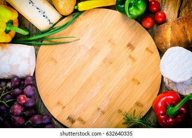 cutting board (copy space) and food ingredients around- cheese, bread, vegetables