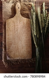 Cutting board and ears of cereals on an old wooden table. Food backgroound.