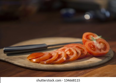 Cutting board with knife and red thinly sliced tomatoes on top. Tomatoes in foreground are in focus but image has a shallow depth of field.  Image has slight bit of noise. Captured at 640 ISO.