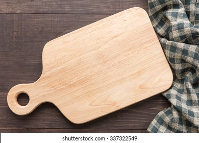 Cutting board with napkin on wooden background.