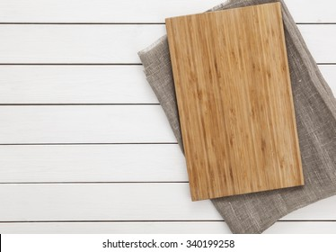 Cutting board and napkin on the wooden background. Top view.
