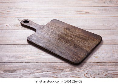Cutting board on the wooden background. Top view mockup
