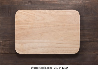 Cutting board on the wooden background. Top view.