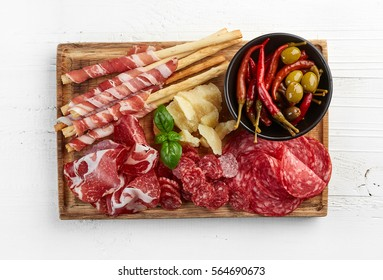 Cutting board with prosciutto, salami, cheese and olives on white wooden background. From top view