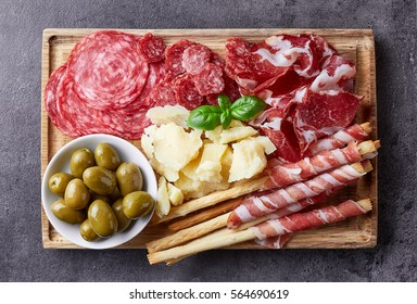 Cutting board with prosciutto, salami, cheese,bread sticks and olives on dark stone background. From top view