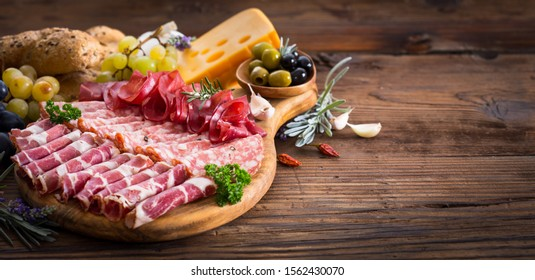 Cutting board with prosciutto, salami, ham, cheese, bread and olives