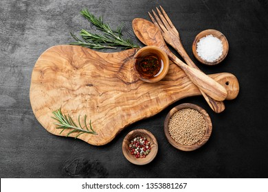 Cutting Board, rosemary and spices on a black wooden table.