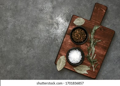 Cutting Board, rosemary and spices on dark table. Empty wooden chopping board. Top view, flatlay
