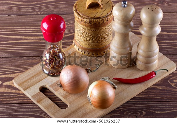 Cutting board with spice,onion,red pepper for cooking on rustic background.