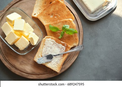 Cutting board with toasts and butter on table
