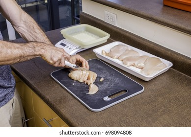 Cutting chicken breast with knife for healthy meal preparation