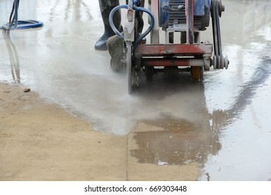 Cutting concrete slabs into grooves with electric saws.
