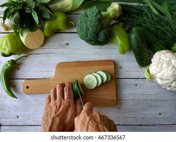 cutting cucumber with green vegetables on the background