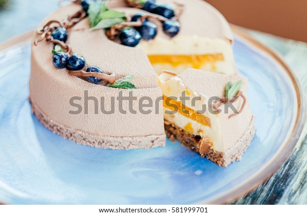 cutting delicious creamy brown cake closeup on blue plate