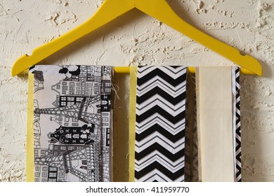 Cutting fabric stripes in yellow, white, grey and black on the yellow clothes hanger behind the stucco background