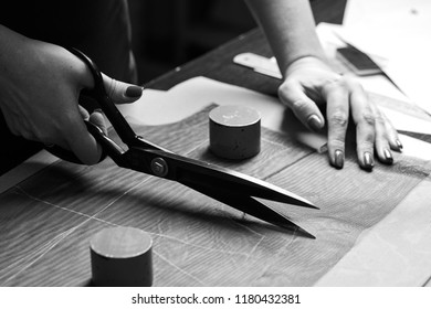 Cutting up the fabric with tailor scissors for further bespoke exclusive fashioning. Tailor atelier - handmade exclusive clothes making and repair, private business, creative occupation concept