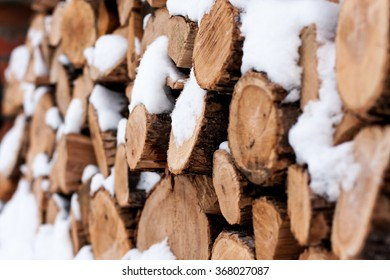Cutting firewood stacked outside in the snow