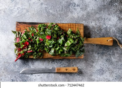 Cutting fresh chard mangold salad on wooden chopping board with knife over gray texture background. Top view with space