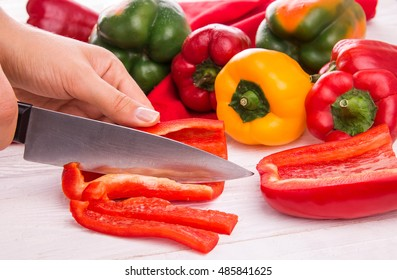 Cutting fresh red pepper on wooden table