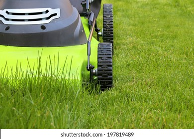 cutting the grass with electric lawn mower