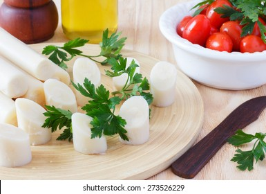 Cutting heart of palm (palmito) with cherry tomato on plate, olive oil and parsley with wooden knife. Selective focus