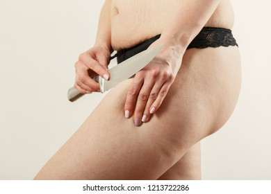 cutting with knife oversized female hip cellulite on white background