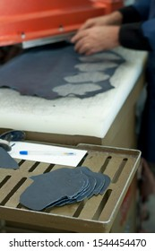 Cutting leather for shoes making. Cutting matrix with shapes cut leather. Shoes factory.