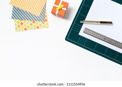 cutting mat board, cuter knife, ruler stainless, Spotted pattern of colored paper, mini gift box. Workspace concept for Creating Gift Boxes on white background with copy space.