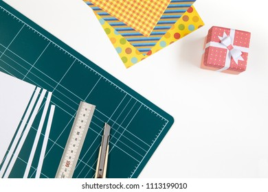 cutting mat board, cuter knife, ruler stainless, Spotted pattern of colored paper, mini gift box. Workspace concept for Creating Gift Boxes on white background.