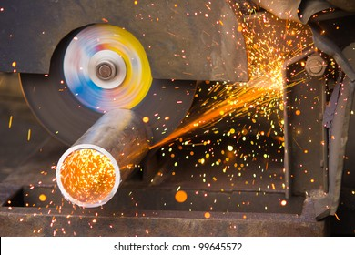 Cutting of a metal pipe with splashes of sparks