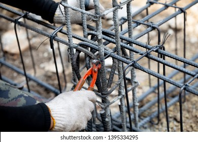 Cutting nipps steel fixer pliers holding on construction worker hand while his hand wear a gloves. Skills worker using pliers to tied together rebar steel with wire rod. Close up and selective focus.
