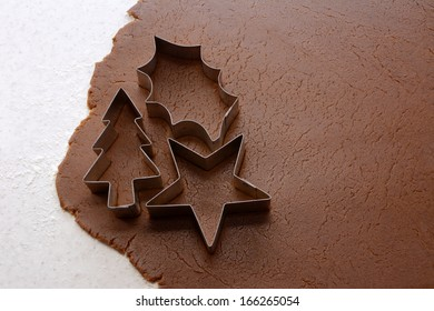 Cutting out Christmas tree, holly leaf and star shapes from gingerbread dough