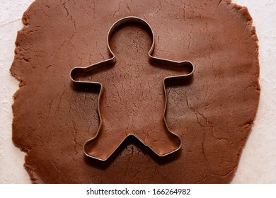 Cutting out a gingerbread man from cookie dough