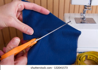 Cutting out a piece of blue fabric with scissors, sewing machine in background