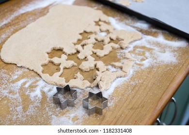 Cutting out star shaped cinnamon Christmas cookies with biscuit cutter and sugar on domestic kitchen bench top