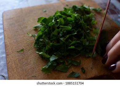 cutting parsley on a wooden board