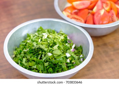 Cutting parsley with tomato background