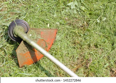 The cutting part of the trimer against the background of freshly cut grass, sunlight, high contrast, bright colors, place for text.