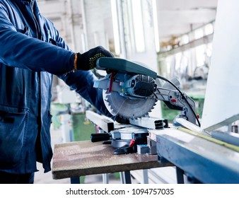 Cutting PVC profile with circular saw. Industrial equipment. PVC windows and doors manufacturing. Background