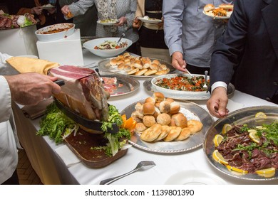 Cutting of raw ham and people served at the buffet