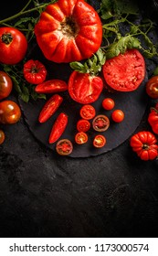 Cutting red tomatoes composition background as knife and tomato bunch on the black background