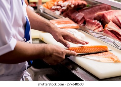 Cutting the salmon with a knife,Japanese chef making sashimi in kitchen,Sushi are made