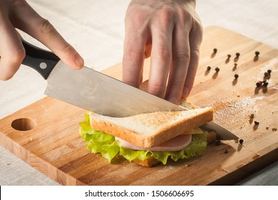 Cutting sandwich with bread, cheese, salad and ham with hands on wooden cutting board with knife