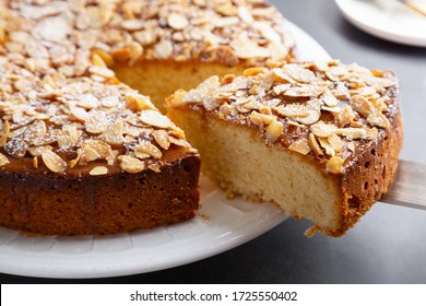 Cutting and serving a portion of almond and lemon cake with sliced almonds topping