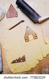 Cutting shapes out of rolled out dough for a gingerbread house, using a cookie cutter.