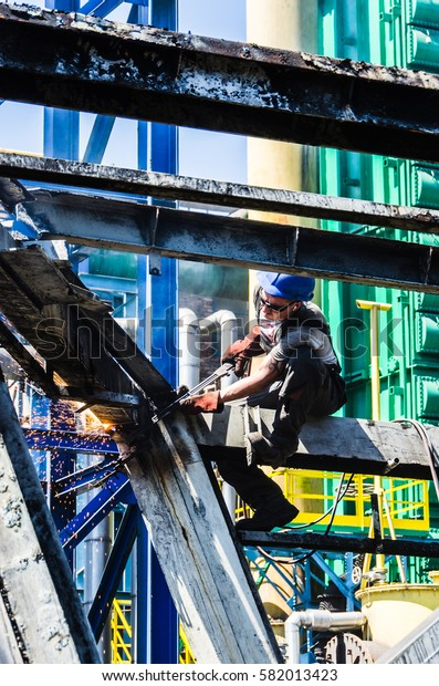 Cutting steel structure. Work at height. Man working on the demolition.