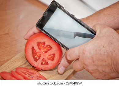 Cutting tomato with knife displayed on mobile phone close up concept
