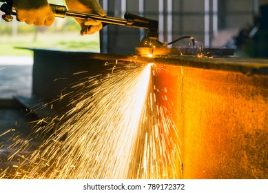 Cutting Torch, Oxygen or Acetylene Cutting Torch, Worker heavy duty cutting metal H-beam structure by acetylene torch with bright sparks in fabrication factory.