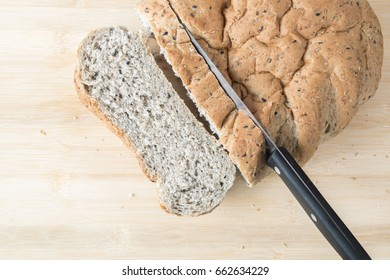 Cutting Whole Wheat Bread, on a wooden background.